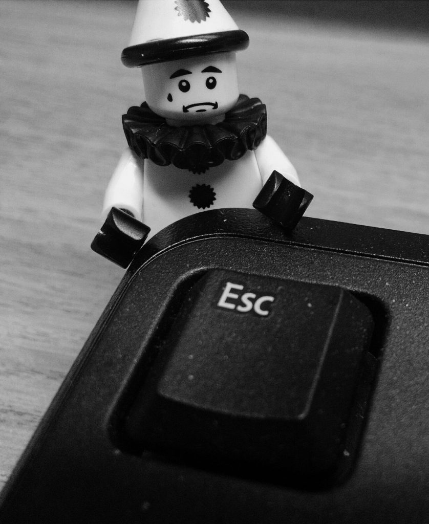 Lego clown depressed and pressing the escape key.
