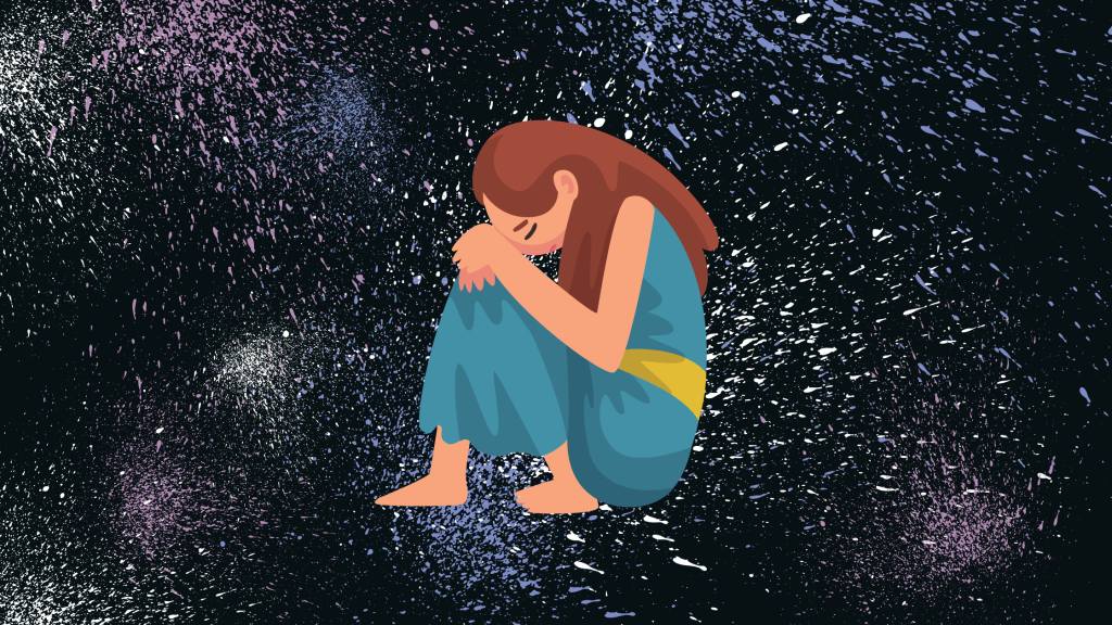 Girl sitting hugging knees and sad surrounded by paint splatters.