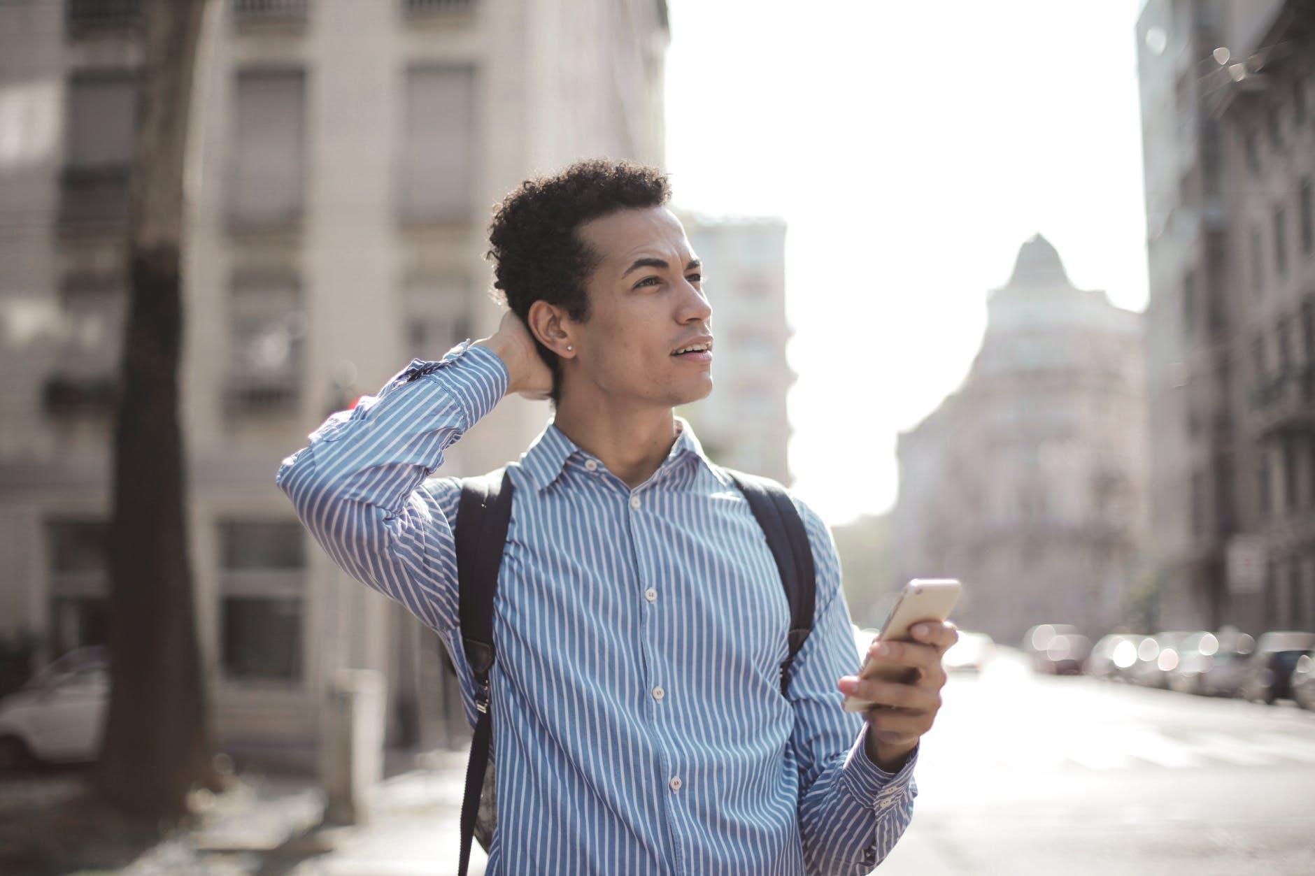 thoughtful man using smartphone on street