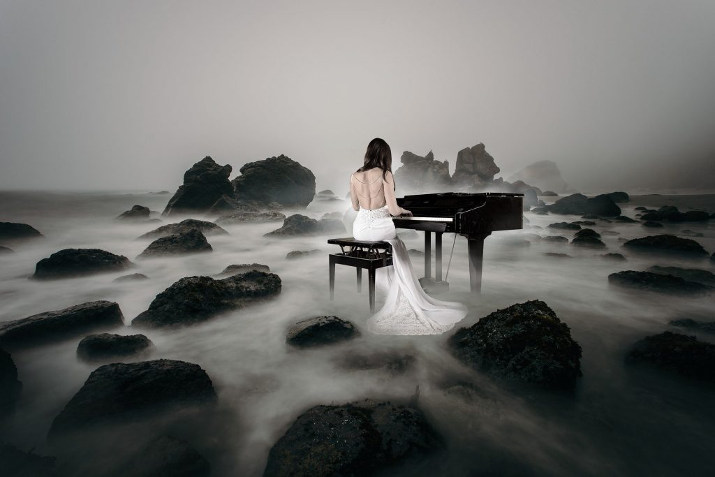 A woman playing the piano in the fog among barren rocks. Your broken parts don't define you even if living with mental illness makes it feel that way. Learn a lesson from a beautiful song about Marilyn Monroe. | #bipolar #feelbroken #mentalillness #chronicillness